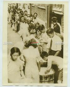 """1937年上海八一三""""淞沪抗战时期,日军占领上海,无家可归的上海市民排队领取米饭救济老照片"""