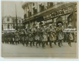 1932年淞沪事变交战时期,英国从香港派遣了阿盖尔和萨瑟兰高地营的三百名军人,来增加租界的安保力量。照片中他们正经过南京西路泰兴路口到大华公寓一带的大华酒店附近