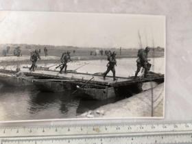 民国抗战时期带着钢盔浮桥上行进的日本鬼子老照片