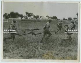 1937年8月日军侵华天津抗战时期,日军与国民党军队交战,一队日本重机枪手抬着武器装备小跑奔向前线老照片