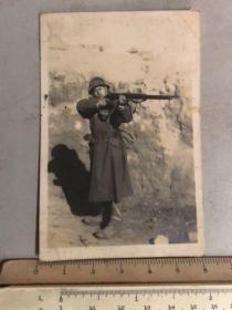 民国抗战时期戴着钢盔拿枪射击的日本鬼子老照片