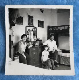 文革时期一家三口合影老照片 桌子上摆放毛主席像、布娃娃,墙上有红色娘子军、白毛女宣传画等,特色非常浓厚
