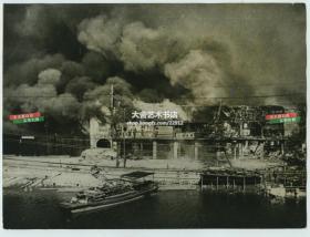 1937年11月淞沪会战时期,著名的四行仓库保卫战刚刚结束,上海苏州河北岸一片残垣断壁,建筑还燃烧着,冒出滚滚黑烟。