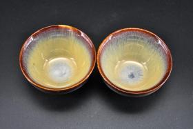 (丙7101)《建盏》一对两件 样式精美 直径约:8.5cm 高度:4.6cm 建盏是中国宋代八大名瓷之一。建盏因产地为宋建宁府瓯宁县,又因瓯宁县为建安附属县,故此称为建盏。