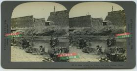 清末民国时期立体照片-------清代晚期北京修建铁路时扒开的城墙,可见城墙内部的结构构造,城外的护城河尚有少许水量,北京百姓在旁边纳凉洗菜