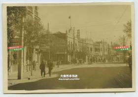 民国时期的天津繁华的大街店铺林立,可见中华馨茶食店等字号,悬挂有国民政府旗帜