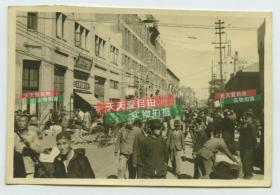 民国1945年左右天津和平路人流熙攘的街道,可见远处中原公司的尖顶,新兴洋服店女子服装专家等招牌。泛银