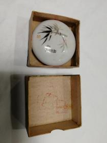 """陶瓷印泥盒。瓷盒盖手绘竹子,有""""精制印泥苏州""""。底款""""中国苏州""""手绘印款。径6cm,盖有一极微飞皮,余全品,印泥可正常用,外纸盒完好。"""