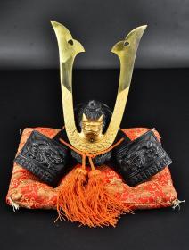 (丙8117)《日本源氏兜》原盒一套全 日本武将兜 金属摆件 带软垫 算立物外框尺寸约:29*20*32cm 总重量:2.73kg 日本武将头上的盔,正式的名子叫做兜,一般都是在平安时代至江户时代形成的,主流的兜一般由麻、木头、竹片、皮革为主要材料,除此之外还配有大量的金属配饰。