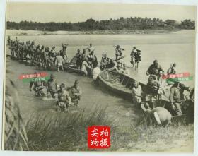 民国1940年日军入侵海南岛,军队士兵人员和辎重等穿越一条较浅的河流老照片。照片尺寸为21.6X17厘米