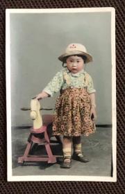 戴草帽穿花围裙的小孩在木马玩具前留影手工上色精美老照片一枚