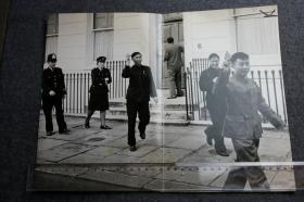 1967年红卫兵烧毁了英国驻北京大使馆后,中国驻英国使馆也遭到了对等报复。照片里中国外交官手举毛主席语录,在英国警察的注视下离开使馆老照片,35.8X27.5厘米