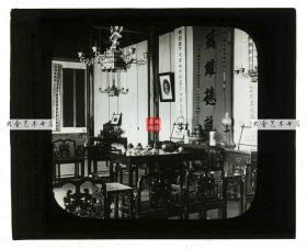 清末民国时期玻璃幻灯片-----民国时期富有中国人家庭的客厅,考究的家具, 中堂对联,吊灯,茶具等陈设,可见悬挂有老辈祖先的照片。