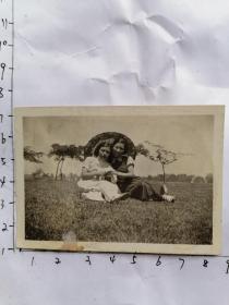 民国老照片:两个旗袍的女孩打洋伞坐在草丛留影