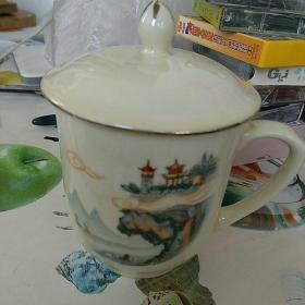 文革〈七十年代〉,瓷茶杯一只〈出口创汇〉。底款:中国烟台 灯塔牌,边沿描金,柴窑厚胎,通高约13㎝,口沿直径8㎝,全新,完整漂亮!