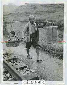 1944年日军侵华时期,一名中国父亲用扁担挑着自己的财产和孩子沿着铁路线行走躲避战乱老照片 (可能拍摄于湖南衡阳或常德一带)