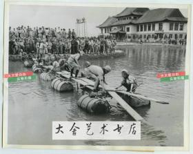 1944年在战争时期的中国童子军用油桶迅速搭建起一座浮桥老照片 ,像成年人一样在战争中担当起了重要的责任。22.8X18厘米。(看背景楼应该是民国某一大学的教学主楼)