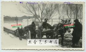 民国时期冬季的天津雪野中,天津百姓艰难地拉车爬坡老照片