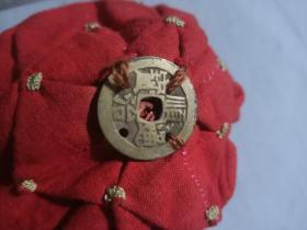 清代小孩帽子上有一枚顺治铜钱。