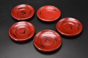 (乙3951)根来涂《日本传统工艺漆器》一套茶托5件全  茶道杯托 木胎漆器 传统造型 茶托直径:11.5CM 高:2CM 公元前二百多年中国的漆艺就开始流传到日本,由于地理环境相似,日本也组织起了漆器生产,形成了日本独特的漆器风格。