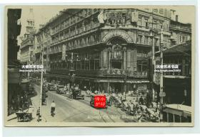 民国时期上海南京路先施公司大楼路口繁华街道街景全貌。可见东亚旅馆中西酒菜的招牌,千里香等, 还有广东南粤食品店。街道上行驶着老汽车以及众多的人力三轮车。照片左侧是著名的新新公司百货大楼。尺寸为13.8×8.9厘米。泛银