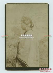 清代服装年轻女子侧脸肖像与发饰橱柜照片一张,照片尺寸为15.5X10.2厘米,粘贴在稍大的照相馆刷金底卡上