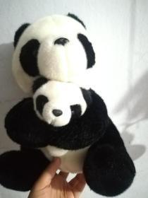 大熊猫抱着小熊猫玩偶玩具
