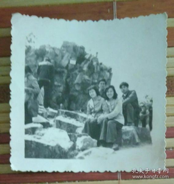坐在假山上的四人照片