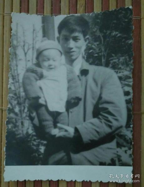 在屋外怀抱幼儿的男子照片