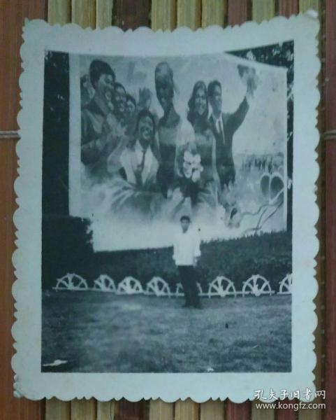站在巨幅宣传画下的男子照片