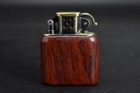 (乙4345)《打火机》一个 外木框为酸枝木 金属件为铜材质 一面雕有关公图案 尺寸:5.72*2.24*4.78cm 全新未使用 火石钢轮打火机产生的火花多 燃点率较高