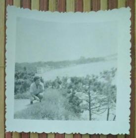 蹲在河边的男子照片