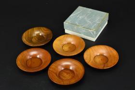 (乙5214)《日本传统工艺漆器》原盒茶托一套五件全 天然木胎漆器 木纹理清晰、不刮手 传统造型 单件直径为:11.7cm 高:2.3cm 公元前二百多年中国的漆艺就开始流传到日本,由于地理环境相似,日本也组织起了漆器生产,形成了日本独特的漆器风格。