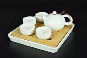 (乙5117)《茶道用具》原盒精装茶具一套 包括:方形茶盘一组,陶瓷底盘、竹制盘面;茶壶一件;茶杯时间 白色干净整洁 茶盘整体尺寸为:21.2*21.2*2.6cm 壶嘴到壶把长度:13.5cm 高:7.55cm 茶杯直径为:5.8cm 高:3.3cm