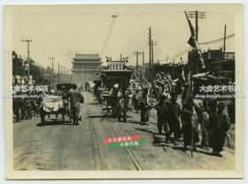 民国早期北京自北向南拍摄的东单北大街和崇文门内大街,远处是崇文门城楼,街道正中有路轨,热闹非凡。泛银