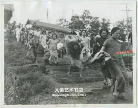 民国1943年四川重庆日军轰炸的警报响起时, 重庆市民拎着自己的贵重财物进入防空掩体中躲避老照片。