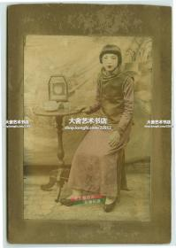 民国早期天足年轻少女肖像照老照片,身边小台子上有钟表,茶壶等物,小褂长袍,难能可贵的是部分红绿手工上色, 恰到好处也算技艺高超了。整件卡纸尺寸15.3X10.4厘米,照片尺寸11.7X8厘米