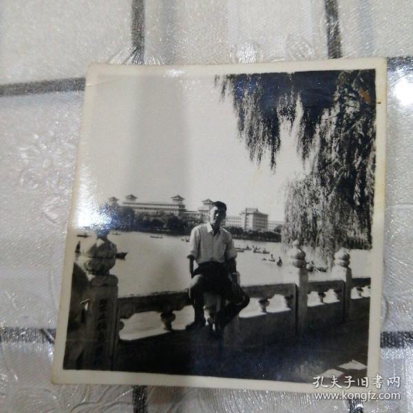 男子北海公园留影(坐栏杆,划船人多)