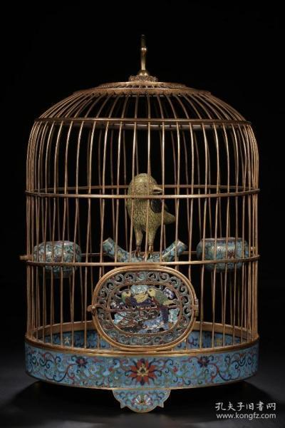 掐丝珐琅鸟笼摆件  高48cm 直径32cm 重量5850g 鸟笼由笼架、托盘、鸟雀、鸟食罐组成。笼架通体鎏金,托盘下承三足,施天蓝色珐琅釉为地,饰緾枝莲纹。鸟雀采用錾胎与掐丝相结合的技法,其中翅膀的轮廓錾胎,羽毛细部掐丝,填施各色珐琅釉。整器釉色纯正,掐丝流畅,鎏金灿然,可以视为乾隆朝掐丝珐琅工艺发展到顶峰的代表作。