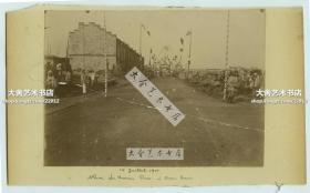 清代1901年八国联军法国军队驻天津兵营附近街道(Baron路) 老照片一张,可见为庆祝7月14日法国国庆而在路上搭建的彩旗和扎花牌楼。尺寸为16.8X12厘米