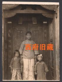 民国老照片,一户高墙大院门前的一位年轻女子和两个孩子合影老照片,精致的门头,门上门芯的对联,衣着打扮,都很有特色