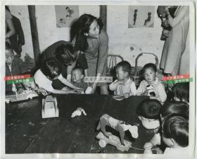 民国1948年中国乡村村镇幼儿园老师照顾孩子们老照片,每个孩子手中都有一件玩具。25.4X20.6厘米