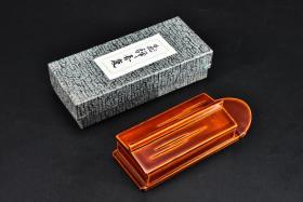 (P8852)《日本传统工艺飞騨春庆涂漆器》原盒漆盒一件  日本漆器 木胎漆器 可装墨条 当做牙签盒、饰品盒等 盒内简洁无图案  尺寸:11.6*4.2*2.8cm 春庆涂指的是涂漆方法和漆器的形状,它的底色为黄、红,上涂多重透明漆,并无过多镶嵌修饰,多是用木板做成的见棱见角的盘、盒、茶托,也用于家具和佛檀上。